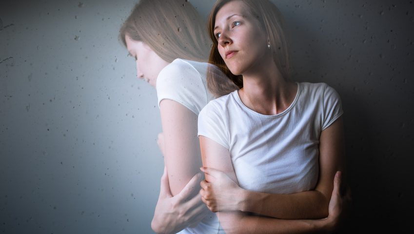 Young woman standing in a corner suffering from a severe depression/anxiety . She has her arms folded & looks sad, stressed & overwhelmed